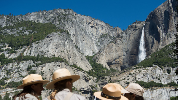 Park rangers meet in front of Yosemite Falls in 2016 in Yosemite National Park, California. Increased fees are expected to boost funding for park maintenance across the country.