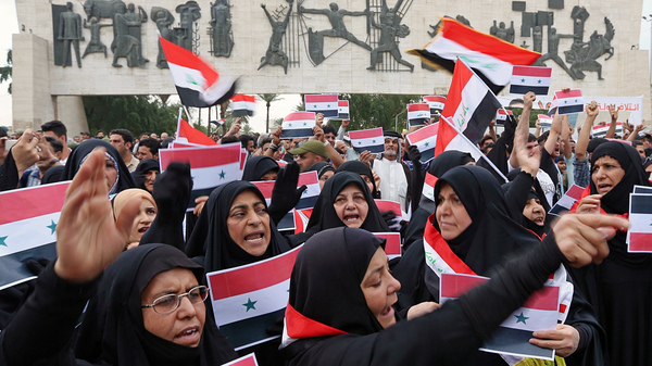 Protesters shout slogans as they wave Iraqi and Syrian flags in Tahrir Square in Baghdad on Sunday.