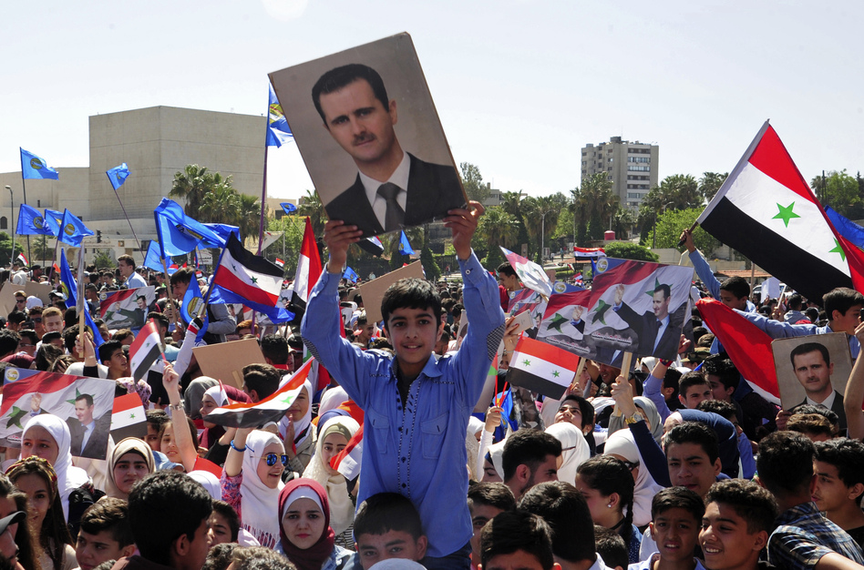 A crowd in central Damascus waves flags and portraits in support of President Bashar Assad on Monday, two days after the U.S., Britain and France carried out airstrikes. The photo was released by the official Syrian news agency SANA. (AP)