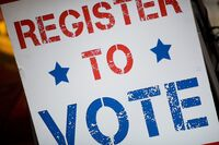 A 2016 file photo of a voter registration sign is seen at a viewing event for the first presidential debate between Donald Trump and Hillary Clinton in Cambridge, Massachusetts. A dozen states have moved or are moving to automatic voting registration.