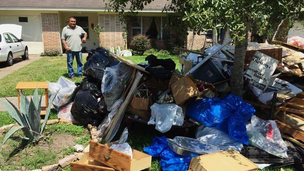 Salvador Cortez, surveys debris in his front yard in Houston after Hurricane Harvey last year.