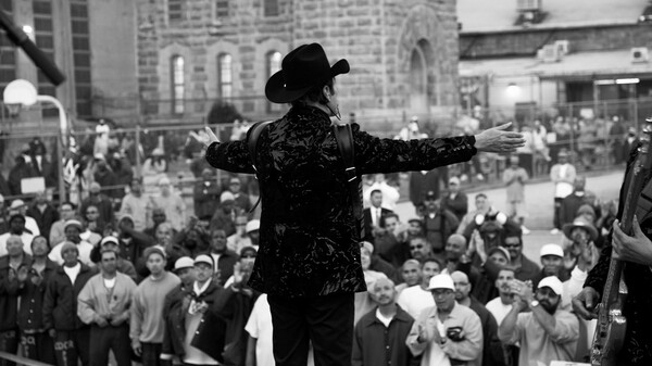 Vocalist and accordion player Jorge Hernández engages the crowd of inmates in the main yard of Folsom State Prison.