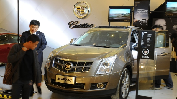 A Cadillac salesmen talks with a potential customer at a shopping mall in Beijing in 2011. This week, China announced moves that could pave the way for new sales for some foreign automakers.