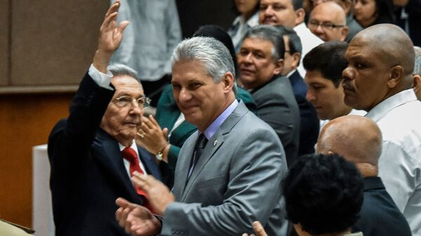 Cuban President Raul Castro waves to the room as First Vice President Miguel Diaz-Canel, Castro
