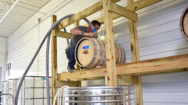 Steve Gagner fills one of the first barrels of bourbon from Danger Close Craft Distilling in St. Albans, Vt.