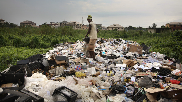 A man sifts through piles of discarded TVs and other electronic waste in a dump site in Nigeria.