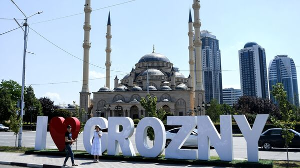 "Young people take a photo in front of the Akhmad Kadyrov Mosque, known as the ""Heart of Chechnya,"" and large letters reading ""I love Grozny"" in central Grozny, Russia, in 2017."