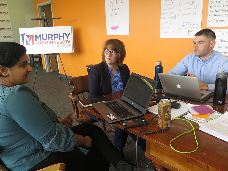 Campaign staff member Aisha Chughtai (left) speaks with Erin Murphy (center), a Democratic candidate for Minnesota governor, at the campaign's St. Paul headquarters as colleague Charles Cox looks on. Chughtai and Cox are members of a newly formed campaign workers union. (Brian Bakst/MPR News)