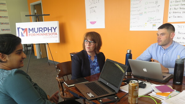 Campaign staff member Aisha Chughtai (left) speaks with Erin Murphy (center), a Democratic candidate for Minnesota governor, at the campaign