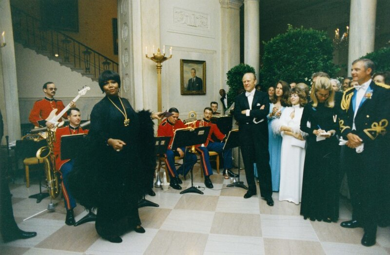 President Gerald R. Ford watches Pearl Bailey perform in the White House Entrance Hall during a State Dinner in May 1975. (Gerald R. Ford Presidential Library and Museum/NARA)