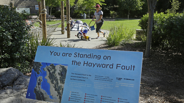 A sign notifying people they are standing on the Hayward Fault stands at the children