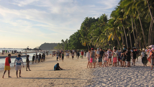 Tourists walk along a beach in Malay town, Boracay, on April 17. President Duterte