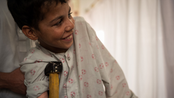 Barkatullah smiles and rests on a crutch and grips his walker during a physical therapy session at Emergency War and Trauma Hospital in Kabul. The 13-year-old lost his right arm and leg in an explosion. He practices standing on the walker 30 seconds at a time.