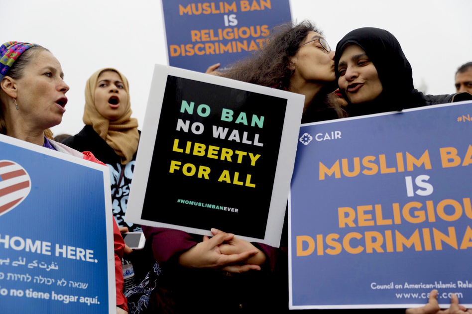 Deeba Jafri gives Hena Zuberi a kiss as they protest in front of Supreme Court on Wednesday as the court heard arguments over the Trump Administration's travel ban. (Tyrone Turner/WAMU)