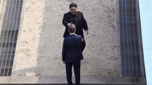 North Korean leader Kim Jong Un, top, approaches to shake hands with South Korean President Moon Jae-in at the border village of Panmunjom in the Demilitarized Zone, South Korea, on Friday.