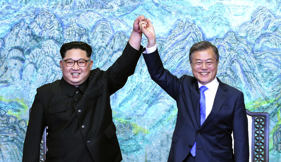 North Korean leader Kim Jong Un, left, and South Korean President Moon Jae-in raise their hands after signing a joint statement at the border village of Panmunjom. (Korea Summit Press Pool/AP)