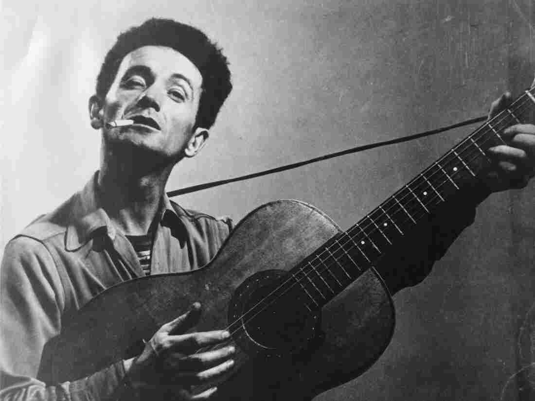 Woody Guthrie playing his guitar, Ca. 1960s.