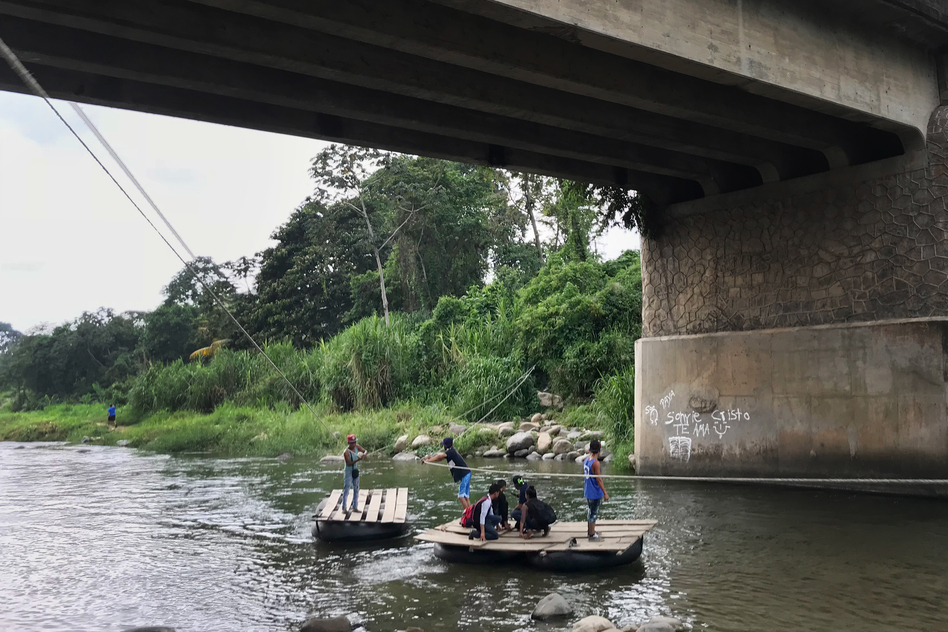 Migrants and day laborers cross the Suchiate River, which divides Mexico and Guatemala. The crossing happens despite immigration officials working on the bridge above. (James Frederick for NPR)