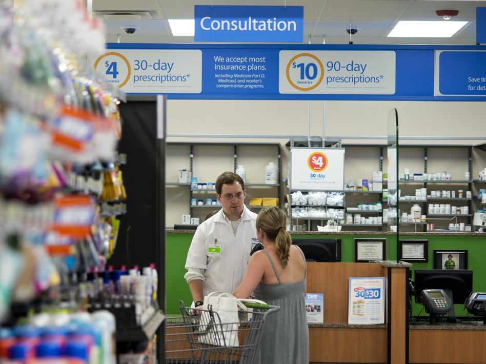 A pharmacist speaks with a customer at Walmart Neighborhood Market in Bentonville, Ark., in 2014. On Monday Walmart introduced a new set of guidelines for dispensing opioid medications. (Sarah Bentham/AP)