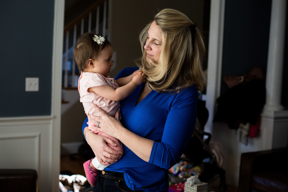 Alicia Nichols holds her daughter Diana in her home in February. After the birth of Diana, Nichols suffered unusual postpartum blood loss that she feels was not taken seriously by her doctor. (Kayana Szymczak for NPR)
