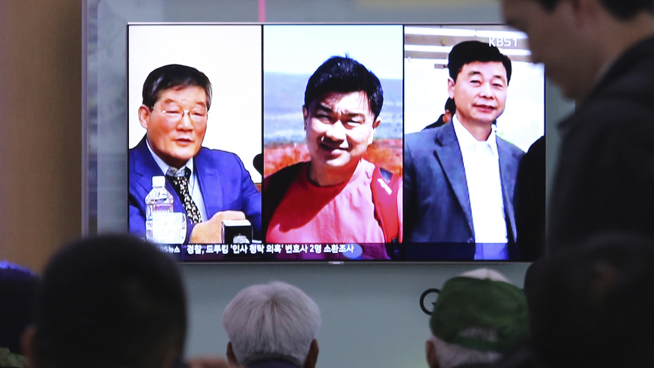 People watch a TV news report in Seoul, South Korea, on May 3, as the screen shows portraits of three Americans detained in North Korea: Kim Dong Chul (left) Tony Kim and Kim Hak-song (right). Three American prisoners in North Korea were released into U.S. custody on Wednesday, according to President Trump. (Ahn Young-joon/AP)