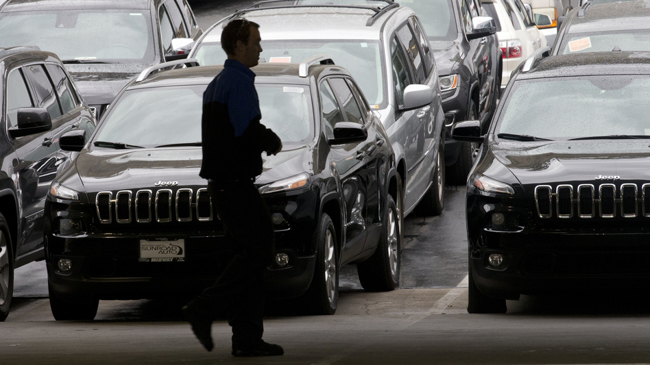 A worker on a Chrysler car lot passes lines of Jeeps in 2014. The House on Tuesday passed a measure to roll back guidance on auto lending issued by the Consumer Financial Protection Bureau. (Gregory Bull/AP)
