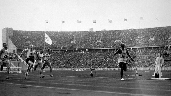 Jesse Owens crosses the line to win the 100-meter dash, one of four gold medals he won at the 1936 Olympics in Nazi Germany. The new book Upon Further Review imagines 31 counterfactual scenarios in sport, including the possibility of the United States boycotting the 1936 games.