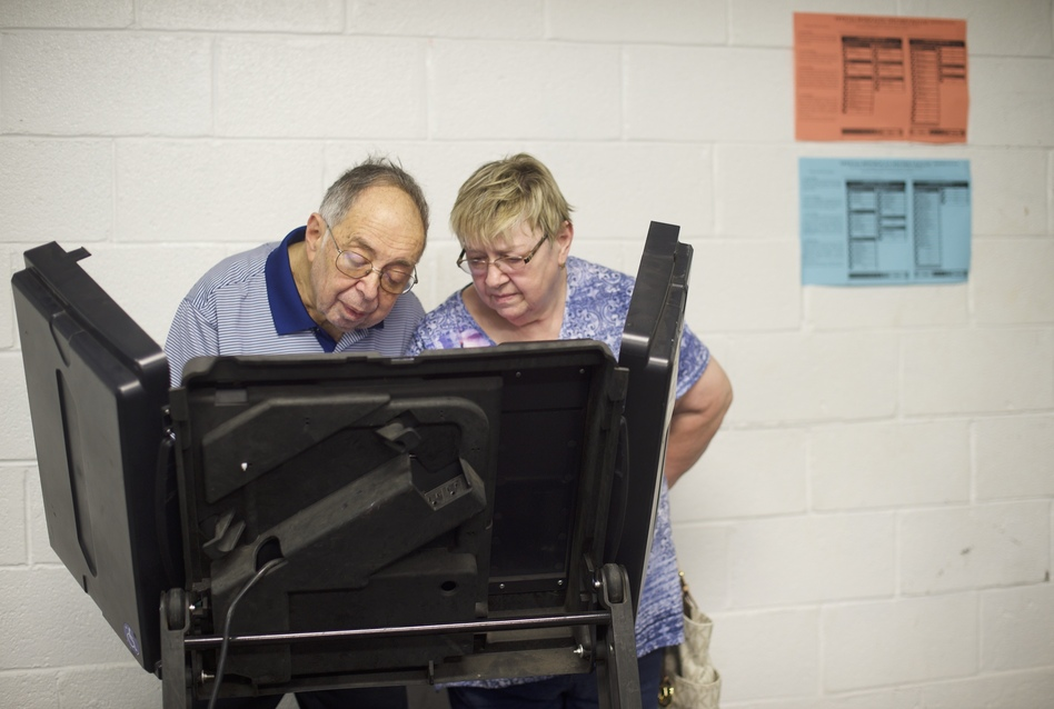 A woman assists a man vote at the Greater Nanticoke Area School District Football Stadium polling station during the 2018 Pennsylvania Primary Election in Nanticoke. (Mark Makela/Getty Images)