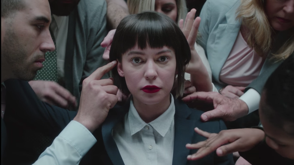 """Coworkers lay hands on singer Meg Myers in a scene from her video for the song """"Numb."""""""