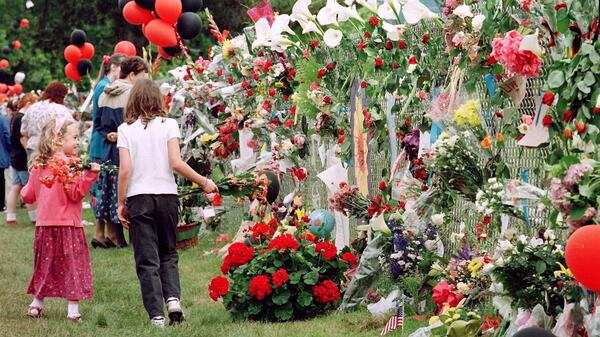 Two girls holding flowers walk along the wall of Thurston High School, serving as a temporary memorial, two days after the shooting.