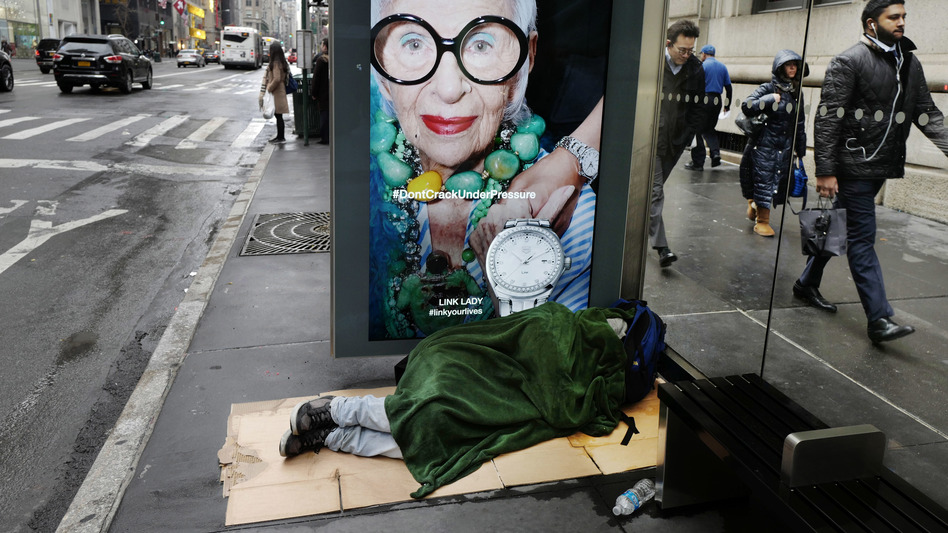 A homeless man sleeps under a blanket in a Fifth Avenue bus shelter in New York. (Mark Lennihan/AP)