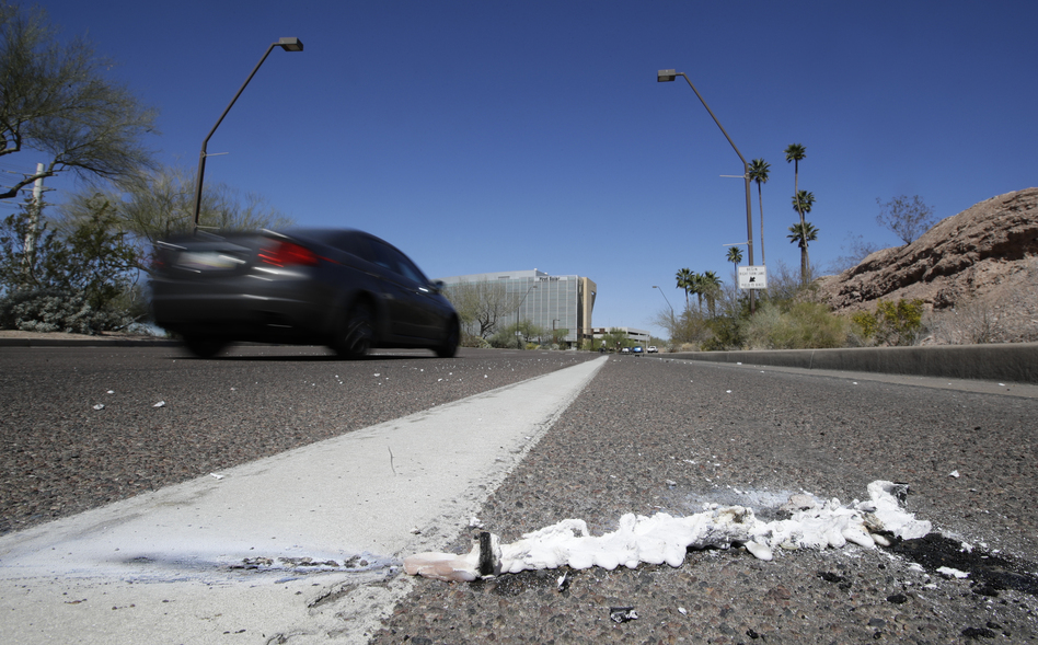 A vehicle drives by the spot where an Uber self-driving vehicle struck and killed a pedestrian earlier this year in Tempe, Ariz. The National Transportation Safety Board released a preliminary report Thursday on the collision. (Chris Carlson/AP)