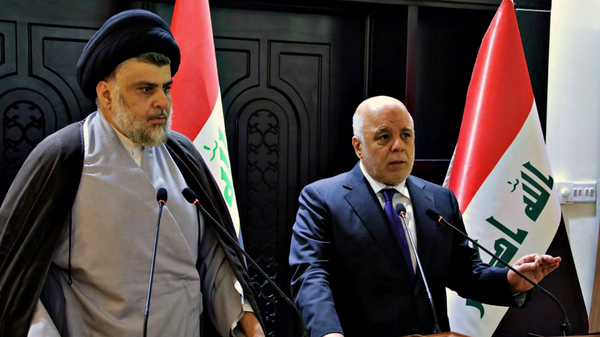In this photo provided by the Iraqi government, Iraqi Prime Minister Haider al-Abadi (right) and Shiite cleric Muqtada al-Sadr hold a press conference in Baghdad on May 20. Sadr