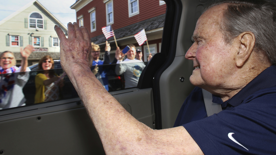 In this May 20 photo provided by the office of George H.W. Bush, the former president waves to supporters as his motorcade arrives in Kennebunkport, Maine. A Bush spokesman said the nation's 41st president was eager to get to Maine after enduring his wife's death and then being hospitalized shortly after that with a blood infection. (Evan Sisley/AP)