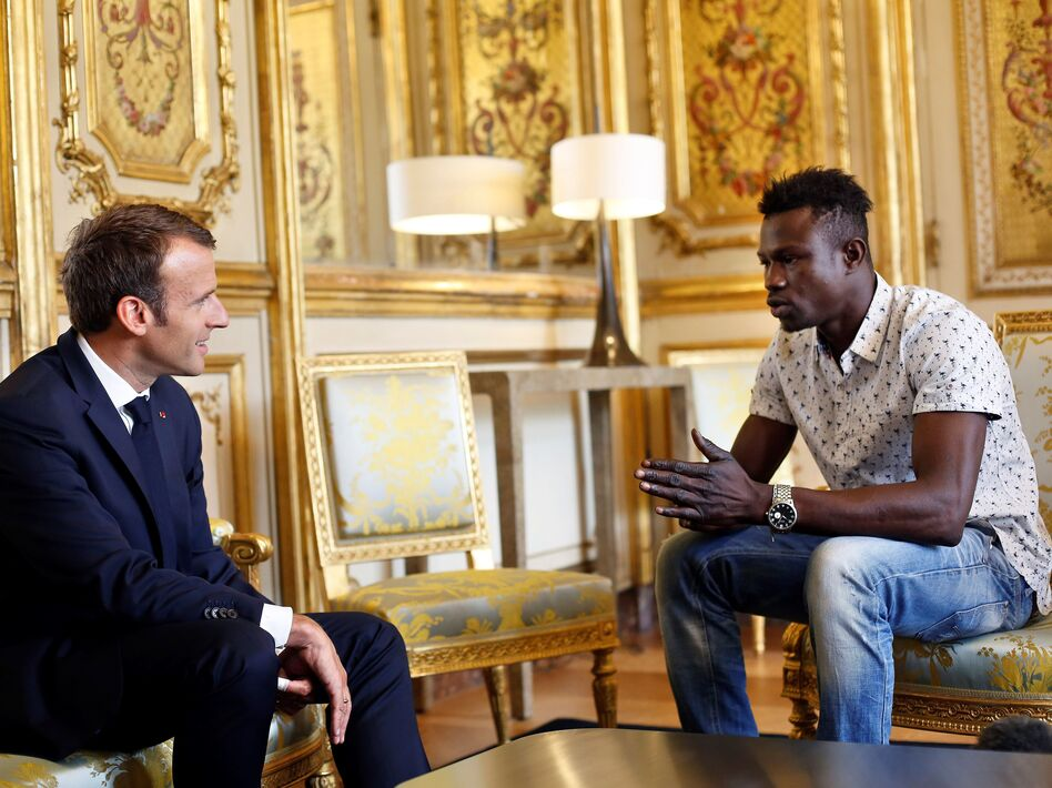 "French President Emmanuel Macron speaks with Mamoudou Gassama at the presidential palace in Paris, on Monday. Macron offered Gassama citizenship for his ""heroic act"" in saving a four-year-old. (Thibault Camus/AFP/Getty Images)"