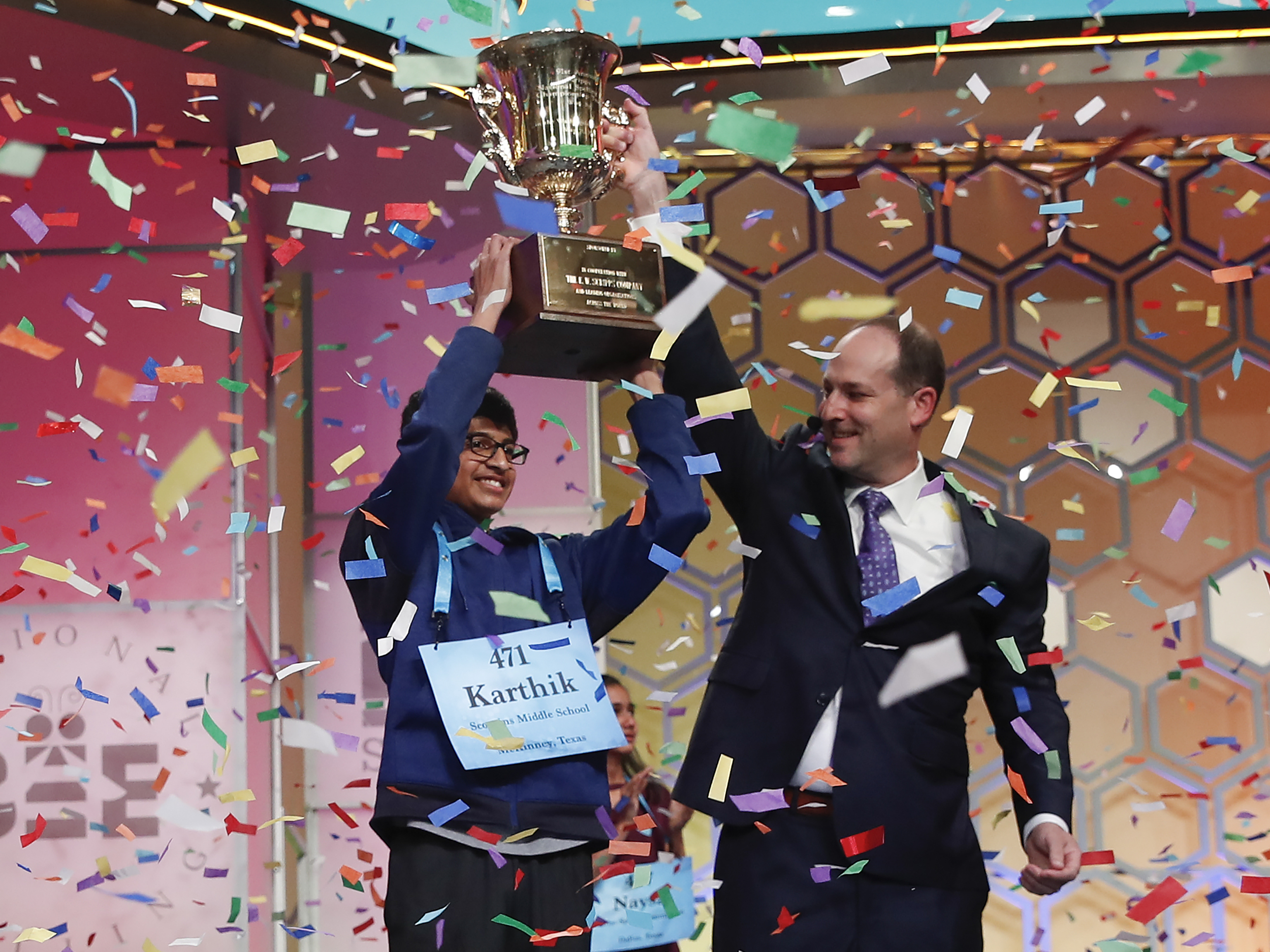 Karthik Nemmani, 14, from McKinney, Texas, holds the Scripps National Spelling Bee Championship Trophy with Scripps President and Chief Executive Officer Adam Symson after winning the annual competition in Oxon Hill, Md., on Thursday.