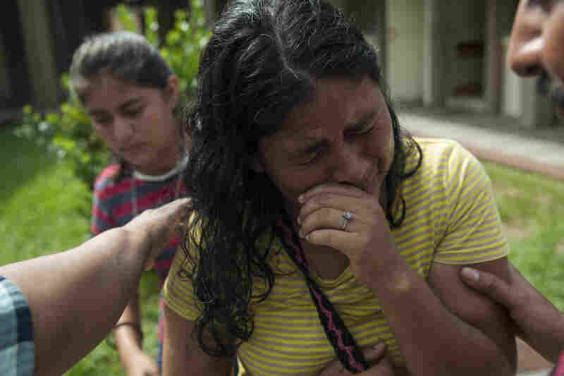 Lilian Hernandez cries as she is comforted by her husband at the Mormon church that has been enabled as a shelter near Escuintla, Guatemala, on Tuesday. Hernandez lost 36 family members in all, missing and presumed dead in the town of San Miguel Los Lotes after the fiery eruption of the Volcan de Fuego, or Volcano of Fire, in south-central Guatemala.