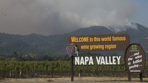 Smoke billows up from a fire burning in the mountains over the Napa Valley last October in Oakville, Calif.