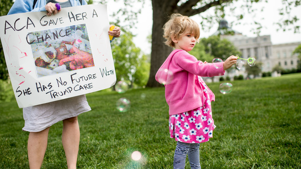 Charlie Wood, right, of Charlottesville, Va., plays with bubbles during a rally near the Capitol to oppose proposed changes to the Affordable Care Act on May 4, 2017. Charlie was born a few months prematurely, and her mother Rebecca, left, fears changes to the health law will negatively affect her care.