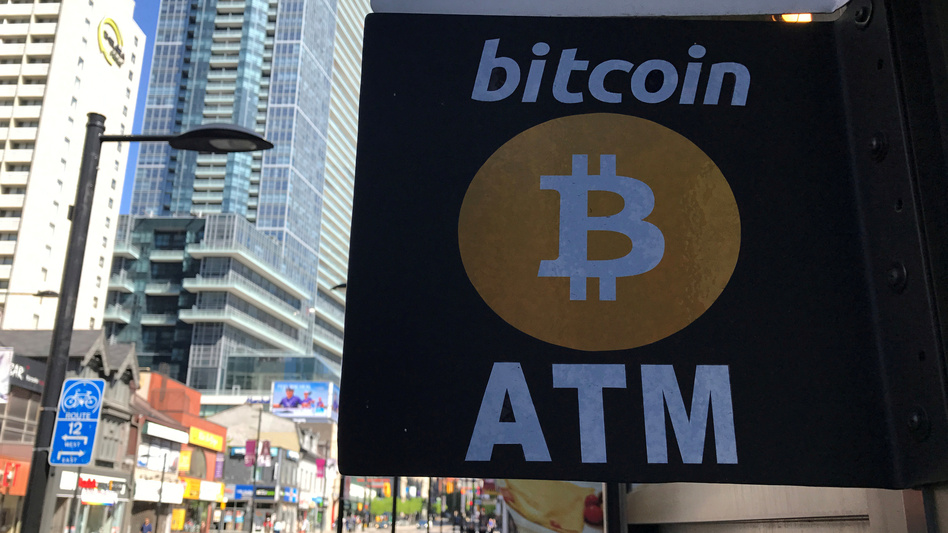 Led by a drop in bitcoin's price, the value of cryptocurrencies fell by more than $40 billion over the weekend and into Monday. Here, a sign advertises a Bitcoin ATM in Toronto, Canada, last summer.