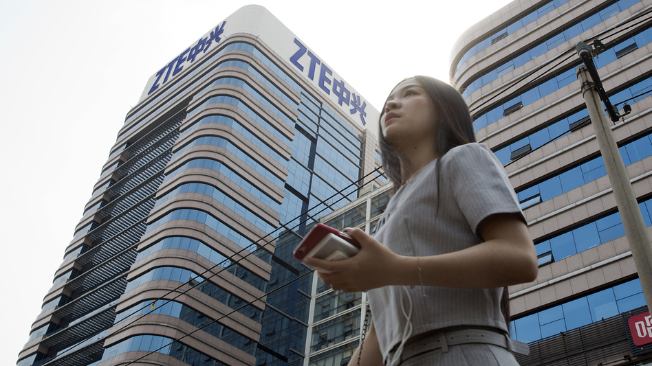 A woman passes by a ZTE building in Beijing, China shortly after President Trump tweeted about possibly reversing a ban on the tech giant in May.