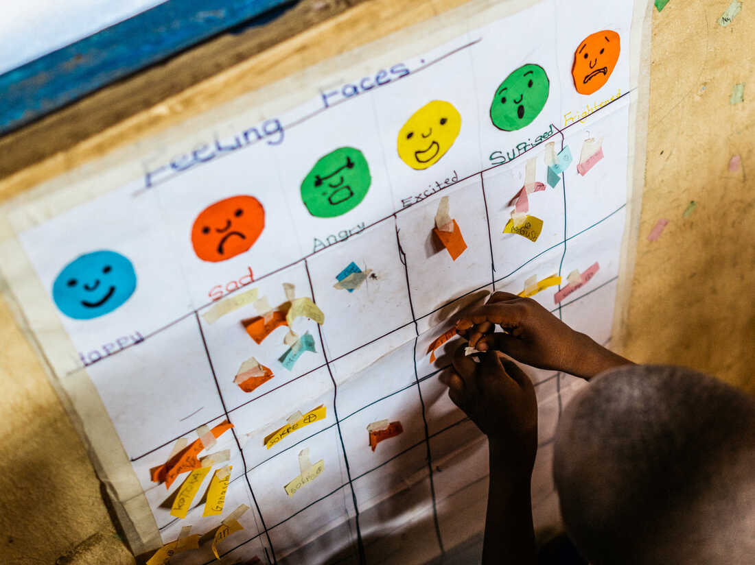 Every day, Godaiva Gbetodeme asks her students to put a sticker under the face that reflects their mood. Then she asks them why they're feeling that way — one of many ways she tries to draw the children out in open-ended conversations.