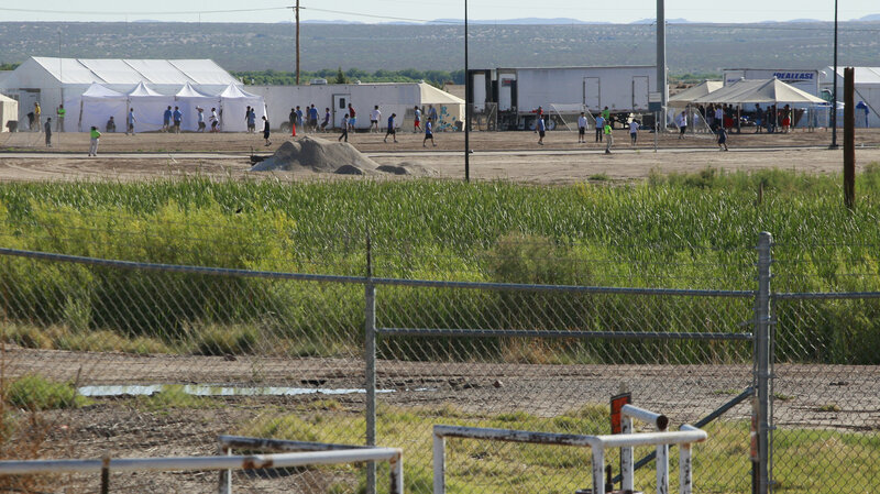 Detained migrant children play soccer at a newly constructed tent encampment as seen through a border fence near the U.S. Customs and Border Protection port of entry in Tornillo, Texas, on Monday. (Jose Luis Gonzalez/Reuters)