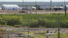 Detained migrant children play soccer at a newly constructed tent encampment as seen through a border fence near the U.S. Customs and Border Protection port of entry in Tornillo, Texas, on Monday.