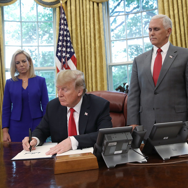 President Trump, accompanied by Department of Homeland Security Secretary Kirstjen Nielsen and Vice President Pence, signs an executive order regarding detaining migrant families on Wednesday at the White House.