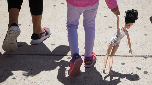 A 4-year-old Honduran girl carries a doll while walking with her immigrant mother. Both were released Sunday from federal detention in McAllen, Texas.