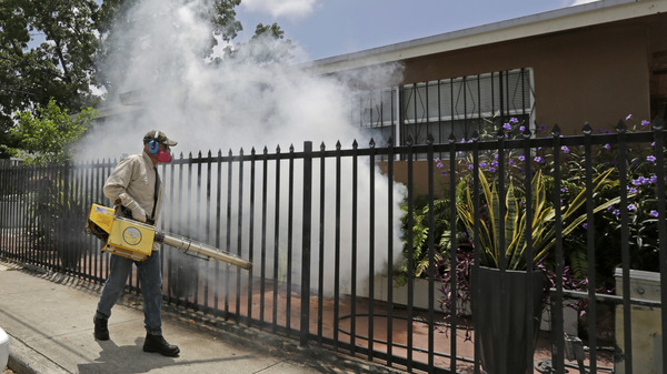 A Miami-Dade County mosquito control worker sprays around a home in August 2016 in the Wynwood area of Miami. A University of Florida study recently identified the first known human case of the mosquito-borne Keystone virus.