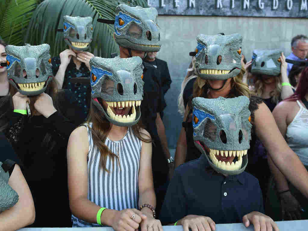 "Fans wear dinosaurs masks waiting for the premiere of ""Jurassic World: Fallen Kingdom"" at The Walt Disney Concert Hall in Los Angeles, California on June 12, 2018."