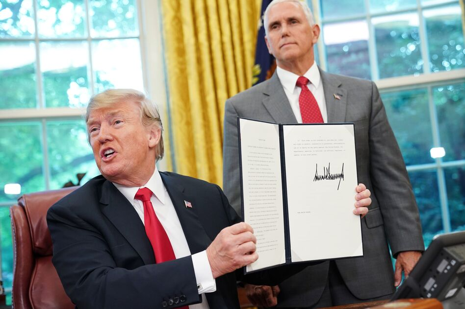 Watched by Vice President Pence, President Trump on Wednesday shows an executive order on immigration aimed at putting an end to the controversial separation of migrant families at the border. (Mandel Ngan/AFP/Getty Images)