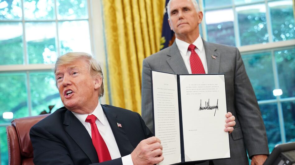 Watched by Vice President Pence, President Trump on Wednesday shows an executive order on immigration aimed at putting an end to the controversial separation of migrant families at the border.